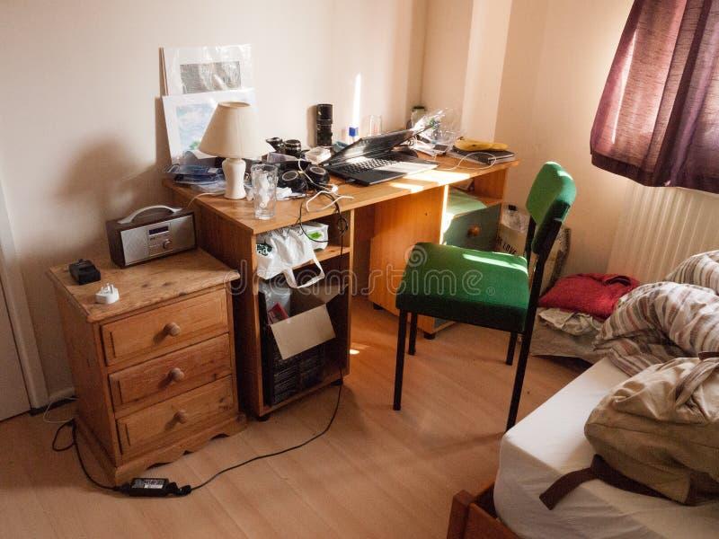 Le bureau et la chaise allumés de chambre à coucher d'étudiant de lumière molle encombrent malpropre image libre de droits