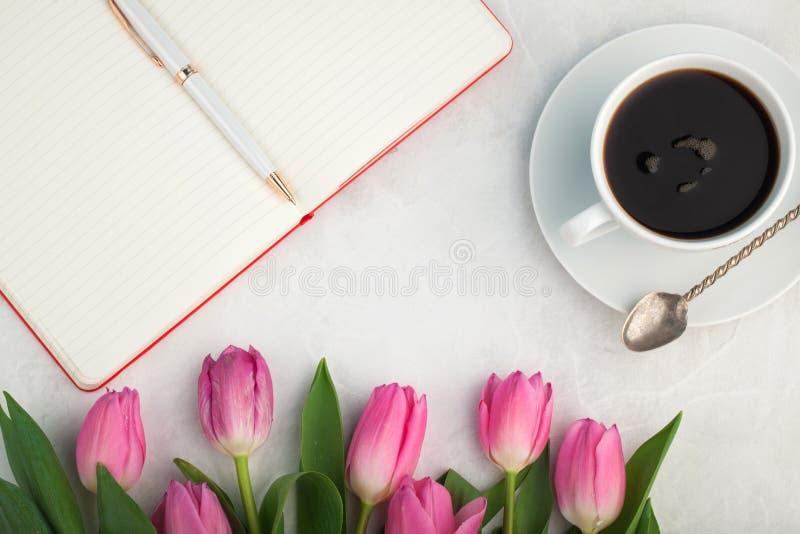 Le bureau fonctionnant de femme avec la tasse de café, le carnet et la tulipe de ressort fleurit la vue supérieure dans le style  photo stock
