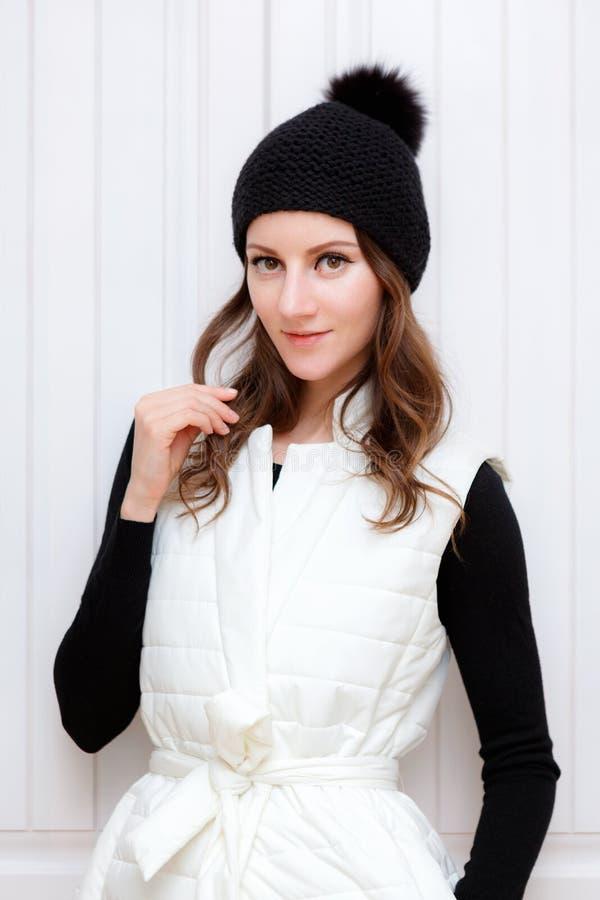 Le butin de fille de brune de style de hippie portant la calotte noire de mode a tricoté le chapeau avec le pumpon de bumbon Hive photo stock
