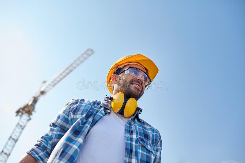 Le byggmästaren med hardhaten och hörlurar arkivbilder
