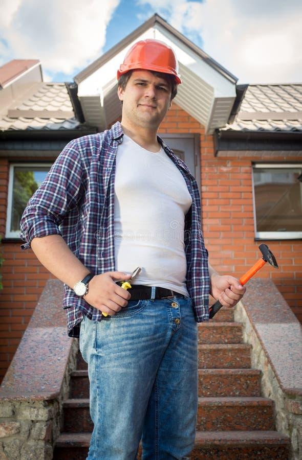 Le byggnadsarbetaren som framme poserar av färdigt hus royaltyfria foton