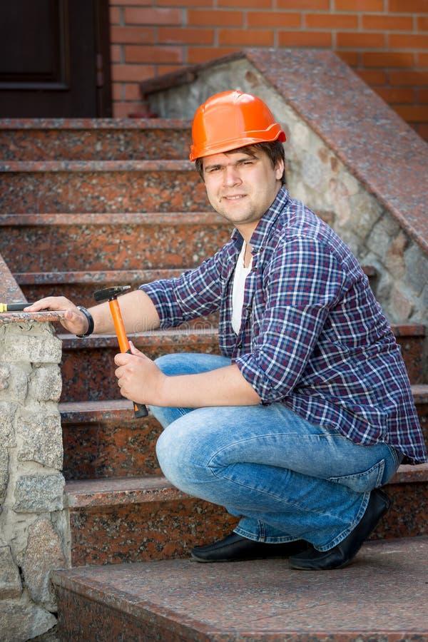 Le byggnadsarbetaren som reparerar stentrappuppgången arkivfoton