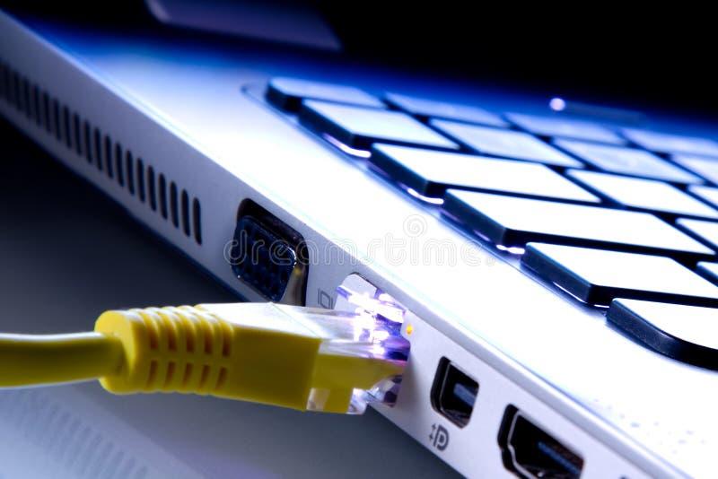Le câble de réseau a branché l'ordinateur portable photographie stock