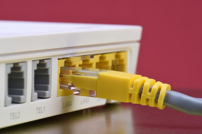 Le câble de réseau s'est relié au routeur d'Internet sur la table en métal photographie stock