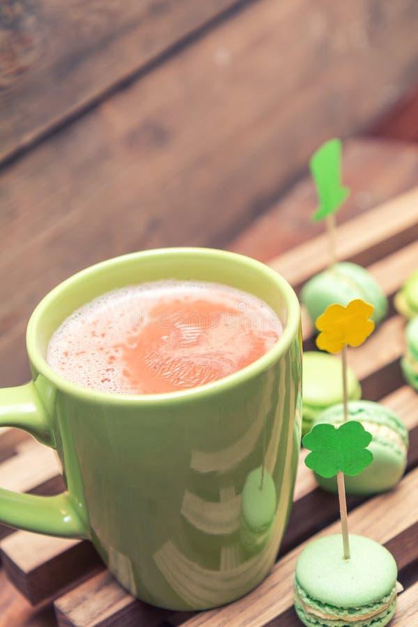 Le cacao chaud en tasse verte et biscuits verts de macaron a dispersé sur t photos libres de droits