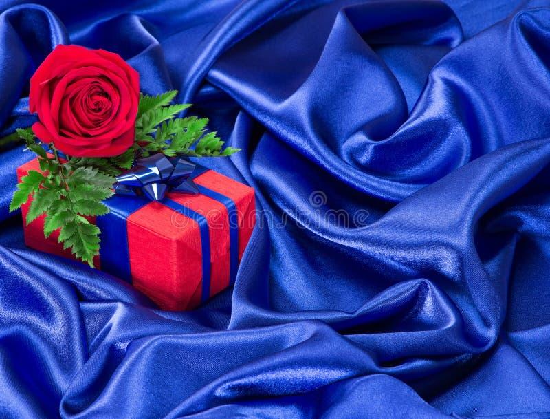 Le cadeau avec s'est levé sur le tissu en soie images libres de droits