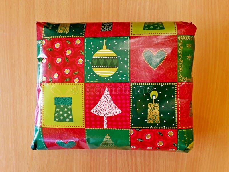 Le cadeau de Noël enveloppé en papier avec des motifs de Noël, s'est étendu sur une table en décor en bois image libre de droits