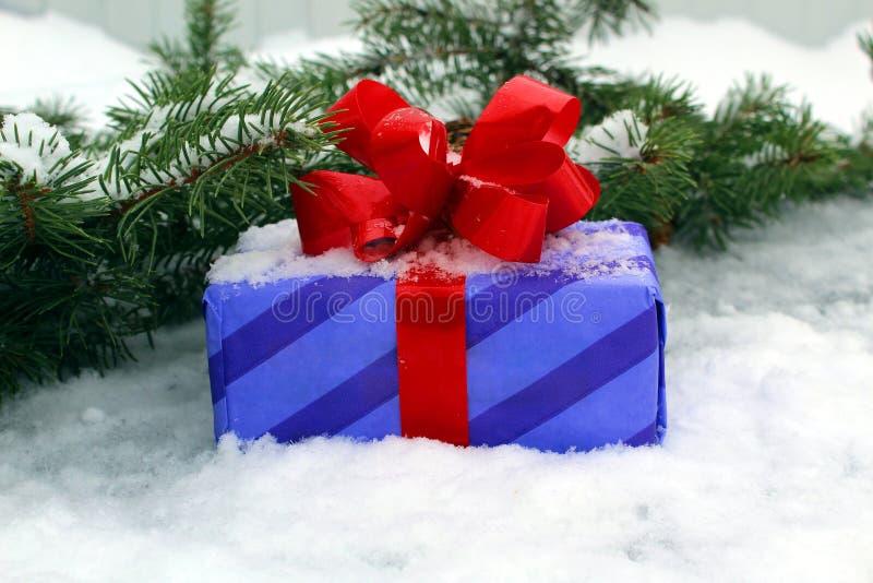 Le cadeau de nouvelle ann?e avec un arc rouge sur le fond de l'arbre et de la neige de No?l images stock
