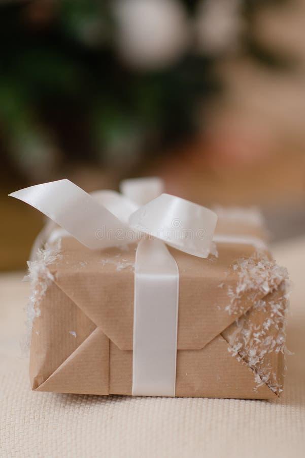 Le cadeau du Nouvel An se trouve près d'un arbre de Noël décoré images stock