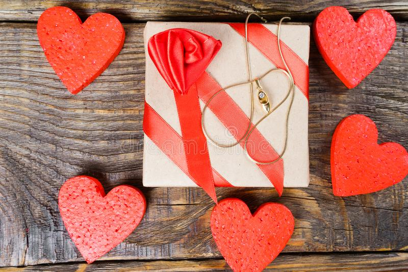 Le cadeau est emballé en papier d'emballage et attaché avec un ruban rouge avec une rose qui a un pendant sous forme d'entraves a image libre de droits