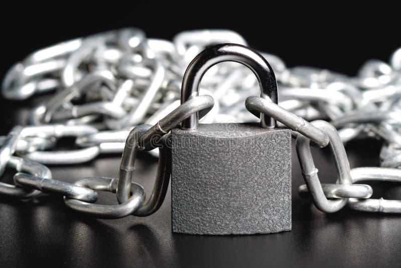 Le cadenas vigoureux ferme deux morceaux de chaîne brillante en métal photos libres de droits