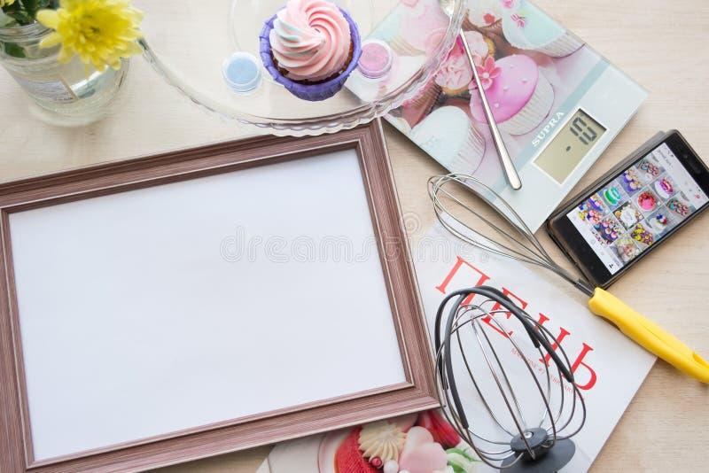 Le cadre en bois avec une feuille de papier blanche se trouve sur le chêne blanchi par table, se trouvant autour des objets : éch photos stock