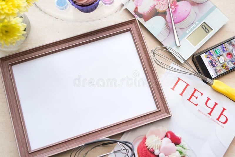 Le cadre en bois avec une feuille de papier blanche se trouve sur le chêne blanchi par table, se trouvant autour des objets : éch photographie stock
