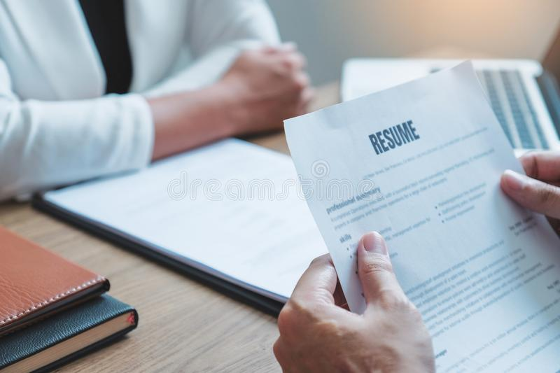 Le cadre supérieur heure lisant un résumé pendant un demandeur et un recrutement de réunion de jeune homme des employés d'entrevu photos libres de droits