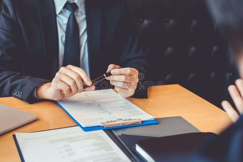Le cadre supérieur lisant un résumé pendant un concept de demandeur et de recrutement de réunion de jeune homme des employés d'en images stock