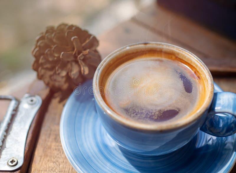 Le café américain chaud est dans une solution en céramique bleue placée sur une table en bois de plancher en café avec de la fumé photo stock