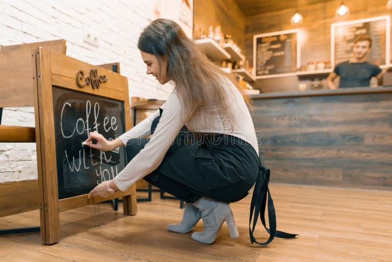 Le café avec vous, écrit dans la craie sur le tableau noir le jeune propriétaire féminin du café photo stock