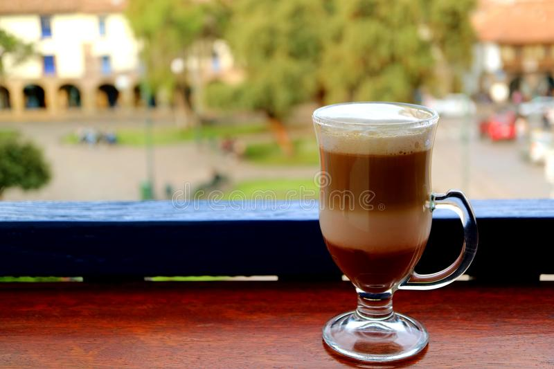Le café chaud de cappuccino dans une tasse transparente a servi à la terrasse avec de la vieille place brouillée de Cusco à l'arr images libres de droits