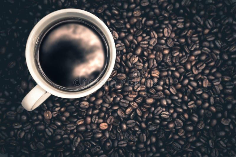 Le café chaud est dans une tasse blanche mise sur le plancher en bois avec des grains de café photographie stock libre de droits