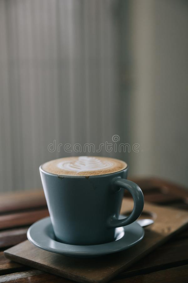 Le café d'art de cappuccino ou de Latte a fait à partir du lait sur la table en bois dans le style de film de cru de café photographie stock libre de droits