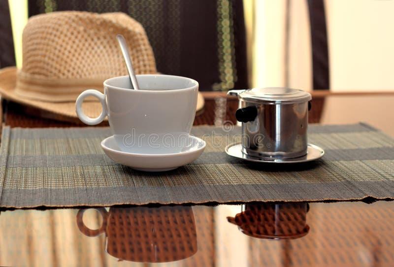 Le café de matin a servi dans le filtre de café vietnamien sur la table de rotin avec un chapeau sur la table photo stock
