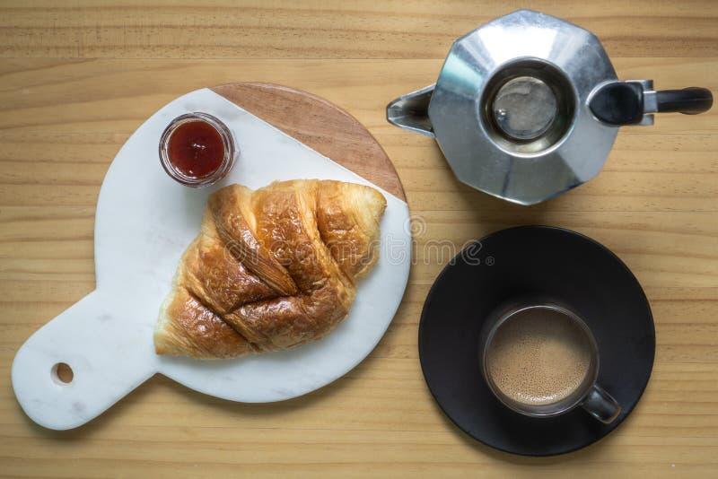 Le café noir avec le creama fait par le brew à la maison de pot de Moka dans la tasse noire d'expresso a servi avec le croissant  images stock