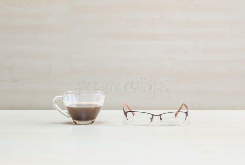 Le café noir de plan rapproché dans la tasse de café transparente avec des lunettes sur le bureau et le mur en bois brouillés a d photo libre de droits