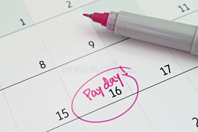 Le calendrier avec le cercle de marqueur rose dans le jour de paie de mot pour rappellent photos stock