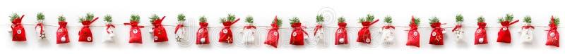 Le calendrier d'avènement de Noël a bourré 24 sachets dans une rangée image stock
