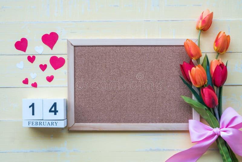 Le calendrier en bois se compose le 14 février des fleurs et les coeurs ont placé côte à côte avec une couleur jaune de fond sur  images stock