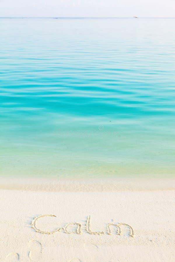Le calme de Word écrit dans le sable sur une plage avec du Ba de mer de matin image libre de droits
