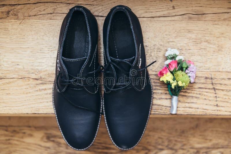 Le calzature dello sposo si trovano sul pavimento di legno ed accanto all'occhiello immagine stock libera da diritti