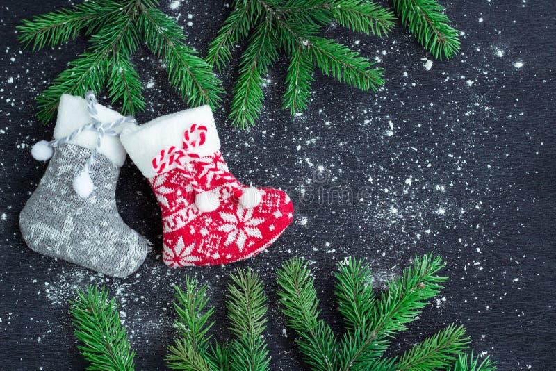 Le calze di Natale accoppiano su fondo nero isolato dalla neve con abete fotografia stock libera da diritti