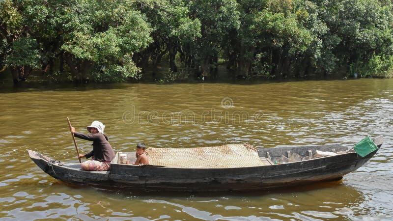 Le CAMBODGE - 28 octobre 2015 : Le garçon cambodgien et sa maman naviguent sur un bateau photo libre de droits