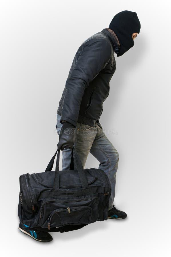 Le cambrioleur ou le voleur masqué avec le passe-montagne part furtivement avec du Ba noir photos stock
