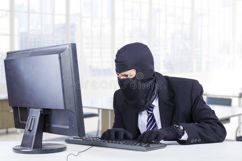 Le cambrioleur vole l'information sur l'ordinateur images libres de droits