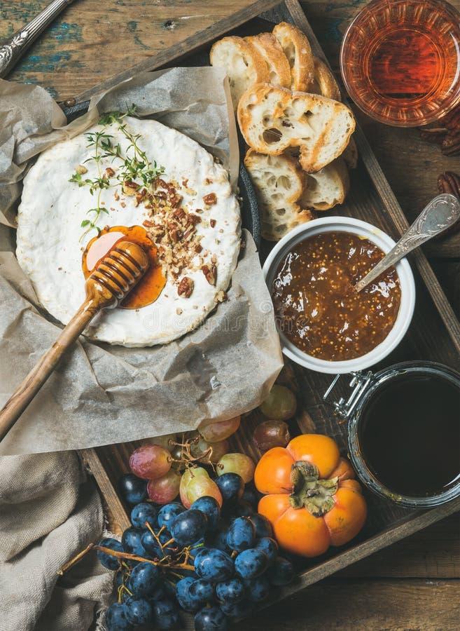 Le camembert, raisins, kaki, confiture de figue, miel, la baguette, verre de s'est levé photographie stock libre de droits