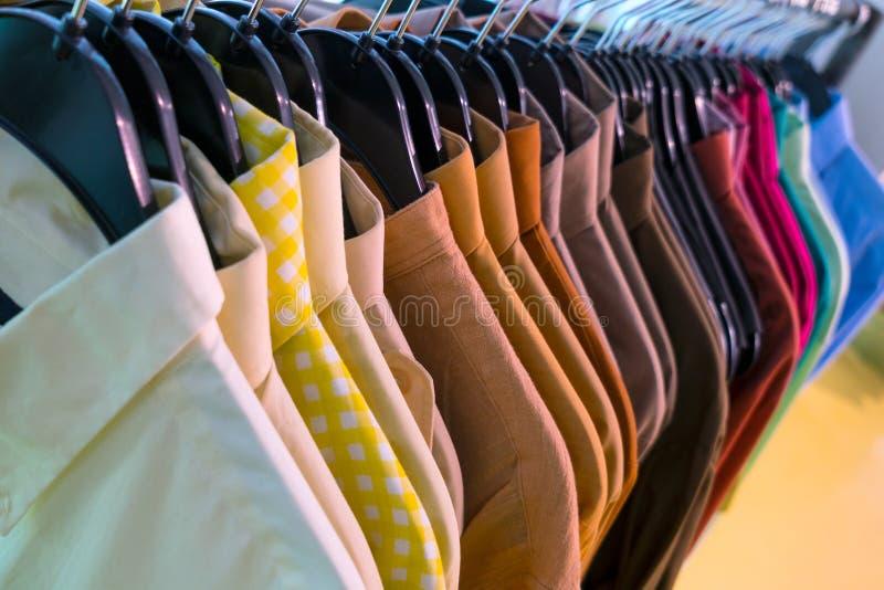 Le camice degli uomini maschii sui ganci in un negozio immagine stock