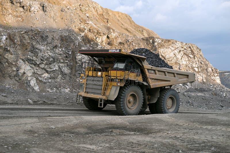 Le camion à benne basculante Caterpillar porte le minerai par une carrière images libres de droits