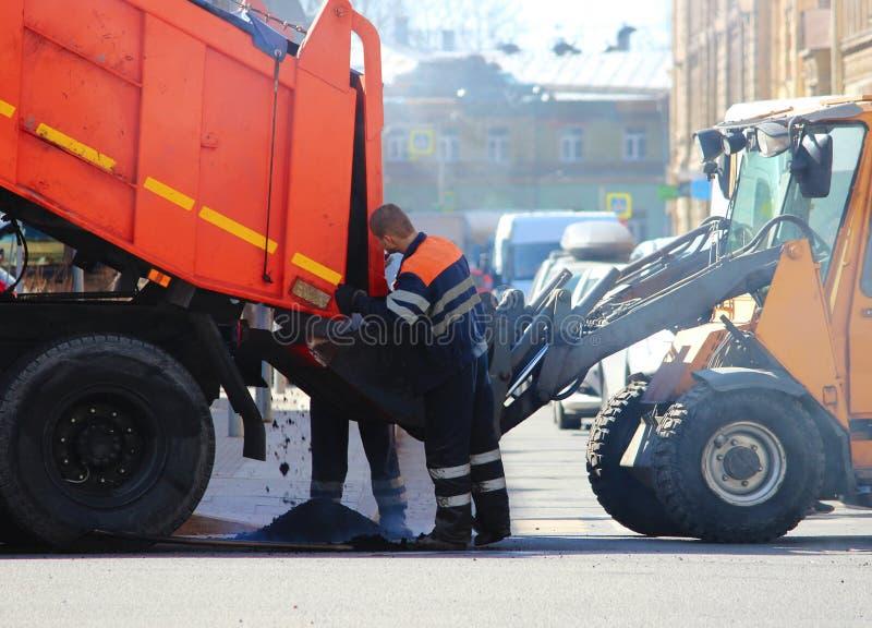 Le camion à benne basculante verse la miette d'asphalte dans le seau d'excavatrice pendant des réparations extrêmes de route tand photo libre de droits
