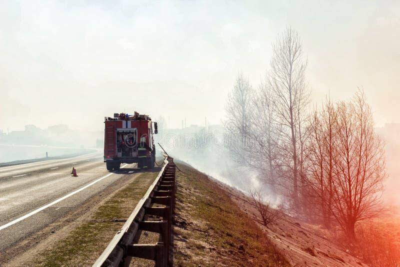 Le camion de pompiers avec un sapeur-pompier sur la route s'éteint un incendie de forêt, fumée lourde, danger photos stock