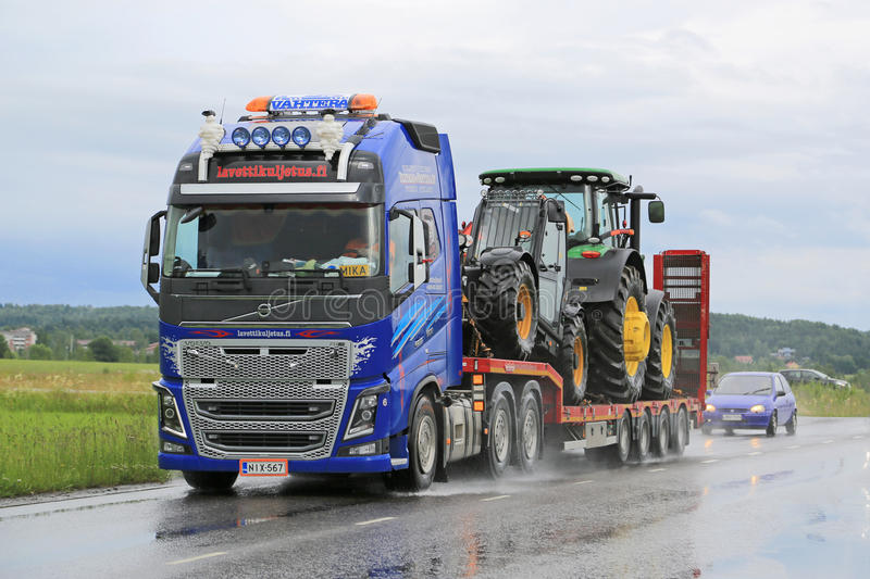 Le camion de Volvo FH16 transporte John Deere Machinery photographie stock libre de droits
