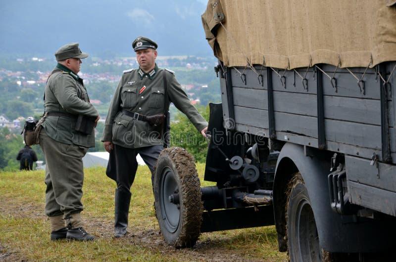 Le camion historique avec deux hommes s'est habillé dans des uniformes nazis allemands pendant la reconstitution historique de la image libre de droits