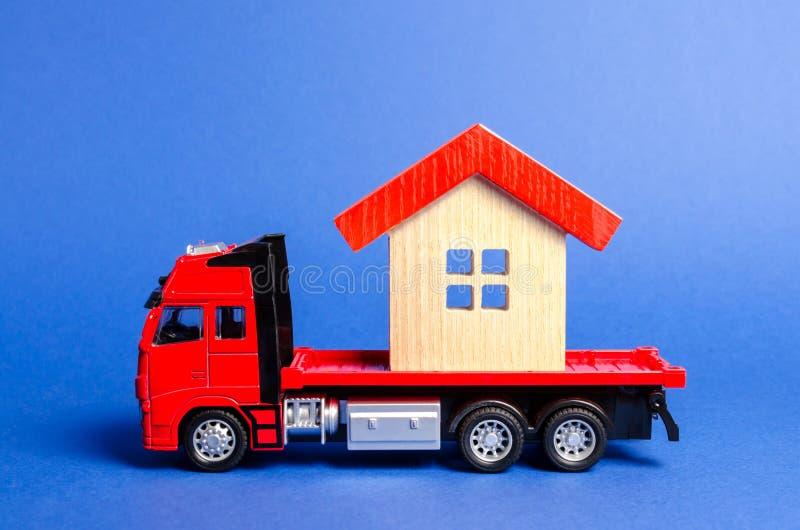 Le camion rouge transporte une maison couverte rouge Concept des transports maritimes de transport et, entreprise de déménagement photo libre de droits
