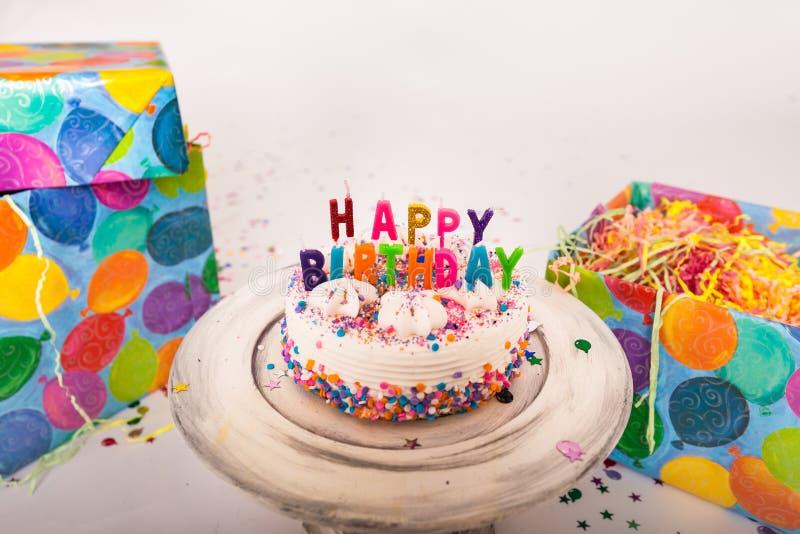 Le candele decorate di buon compleanno della torta di compleanno sul supporto del dolce hanno avvolto i regali su fondo solido fotografie stock