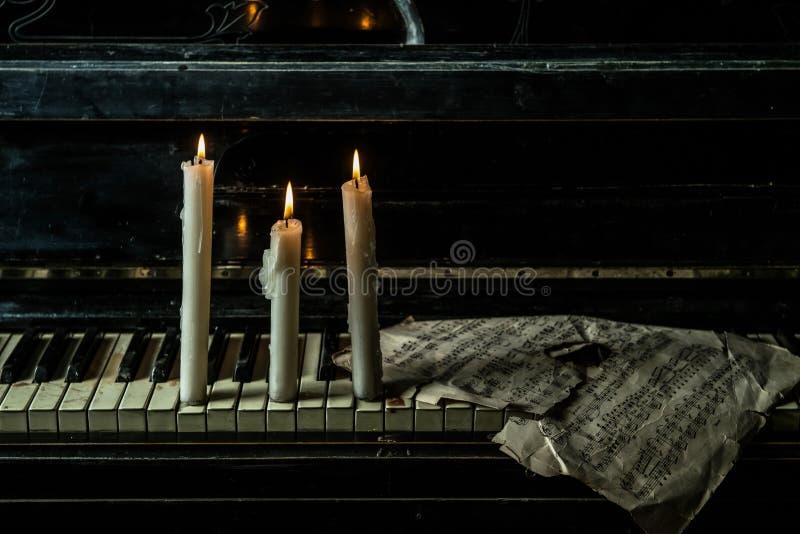 Le candele sono accese sul piano con musica immagini stock
