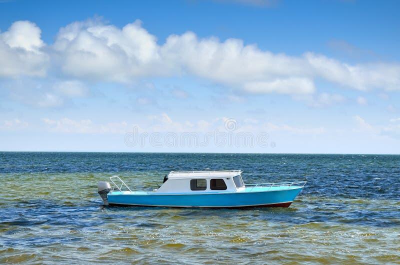 Le canot automobile sur la mer ondule contre le ciel bleu photo stock