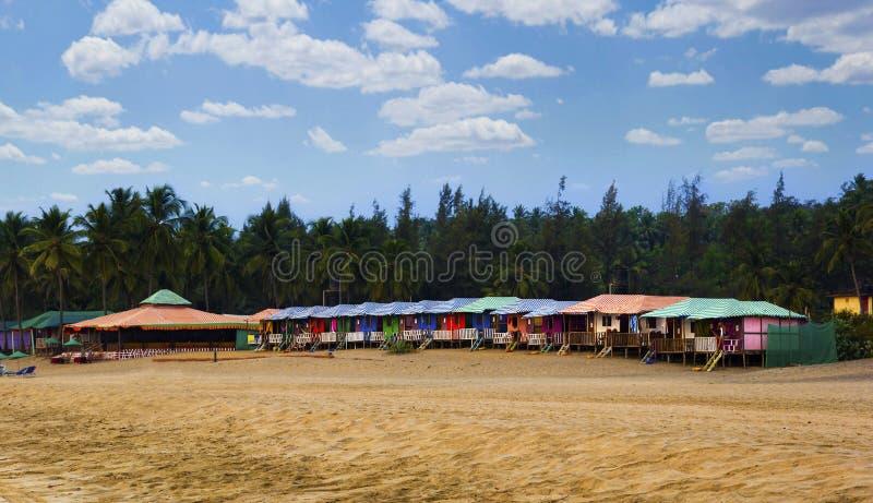 Le capanne variopinte in Agonda tirano con il fondo delle palme in Goa, India immagine stock