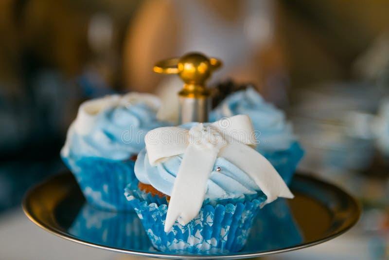 Le capcake bleu savoureux sur l'obscurité a brouillé le fond, photo dénommée de nourriture images stock