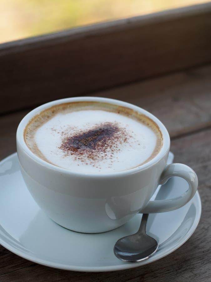 Le cappuccino chaud avec la pleine bulle fine crème peu de poudre de cacao a servi dans la tasse de café en céramique blanche image libre de droits